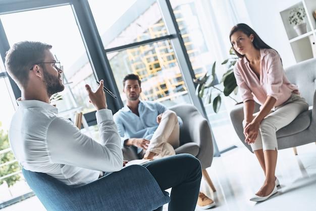 カップルセラピー。セラピーセッションに座っている間心理学者に耳を傾ける若い夫婦