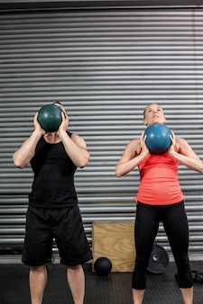Couple throwing ball in the air at gym