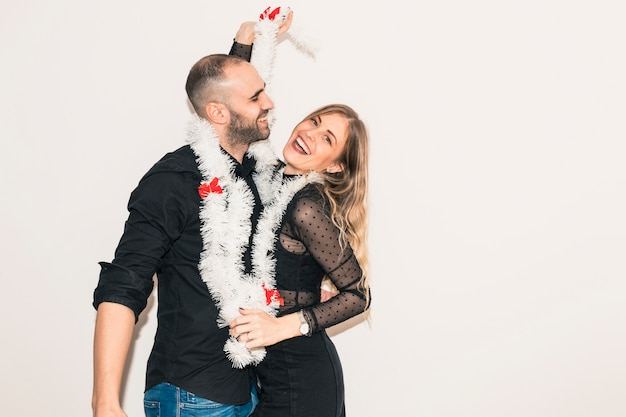 Couple in tinsel dancing at party