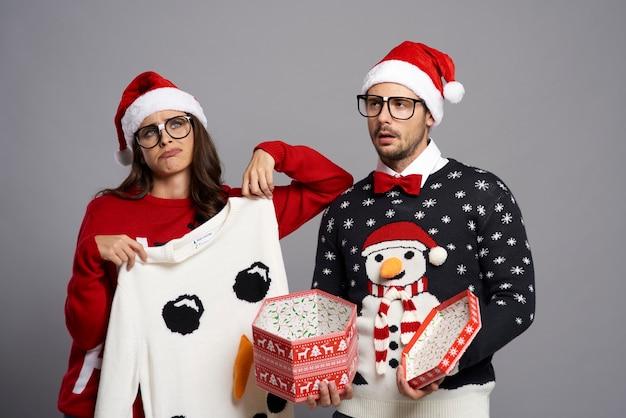退屈なクリスマスプレゼントにうんざりしているカップル