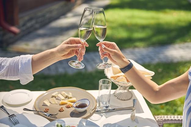 낭만적 인 저녁 식사 동안 레스토랑 테이블 위에 와인 잔을 토스트하는 부부 프리미엄 사진