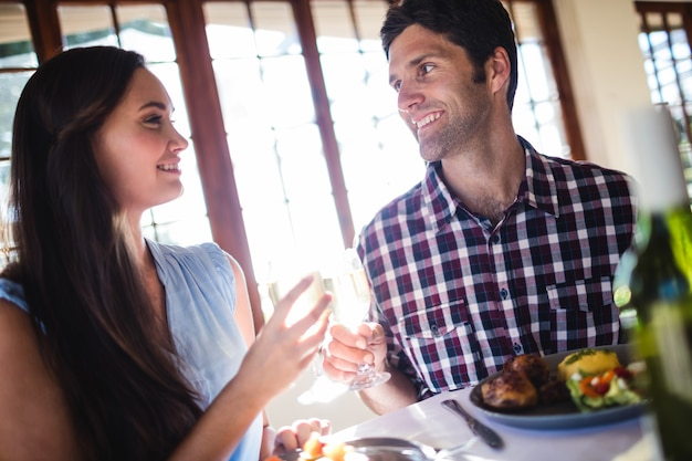 Couple toasting white wine glass in restaurant