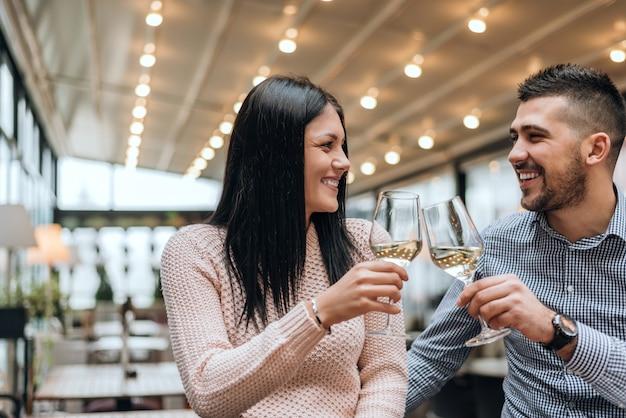 Couple toasting wine glasses at restaurant.