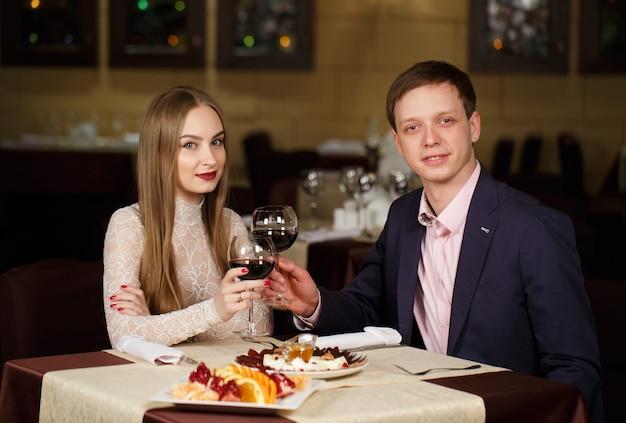 Пара поджаривает бокалы в роскошном ресторане.