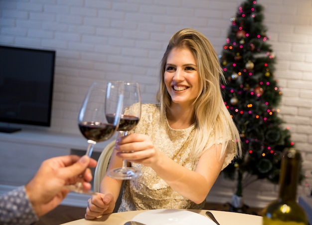 Couple toasting with a glass of red wine at new year's or christmas night