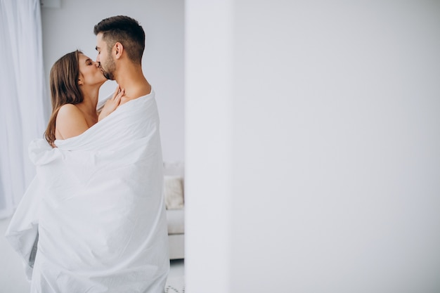 Пара вместе обниматься под белым одеялом