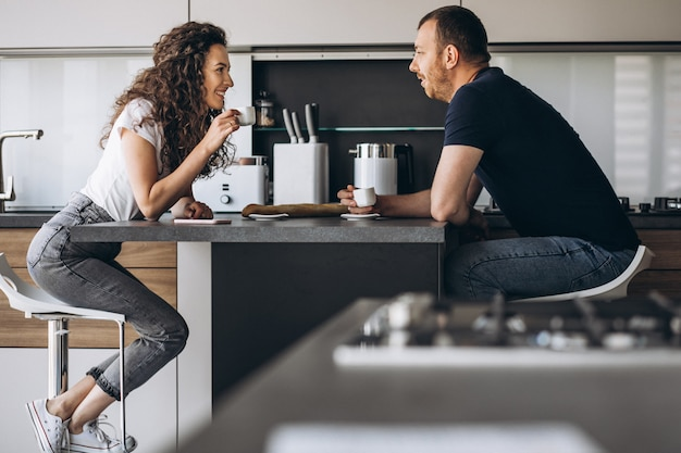 Couple together at the kitchen drinking coffee