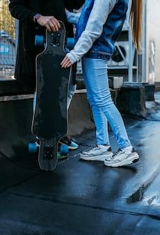 Coppia insieme all'aperto con lo skateboard