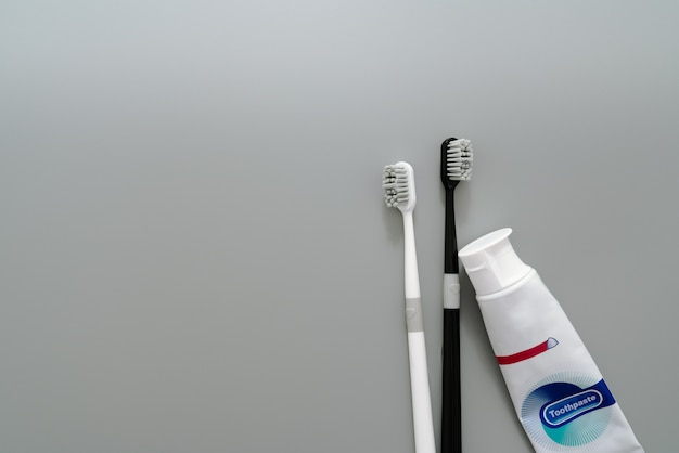 Couple of toothbrush with toothpaste on gray background, healthcare concept