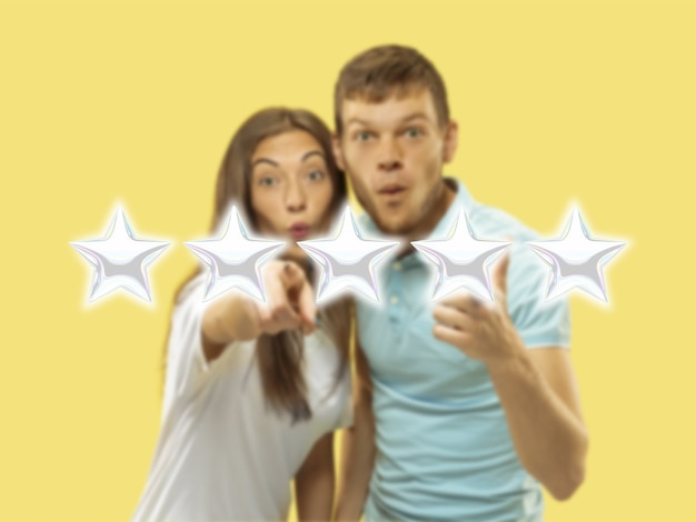 Couple touching five star symbol to increase rating of company, app or service. leave rate for product, specialist, programm. concept of business, tech, marketing, advertising, sales, communication.