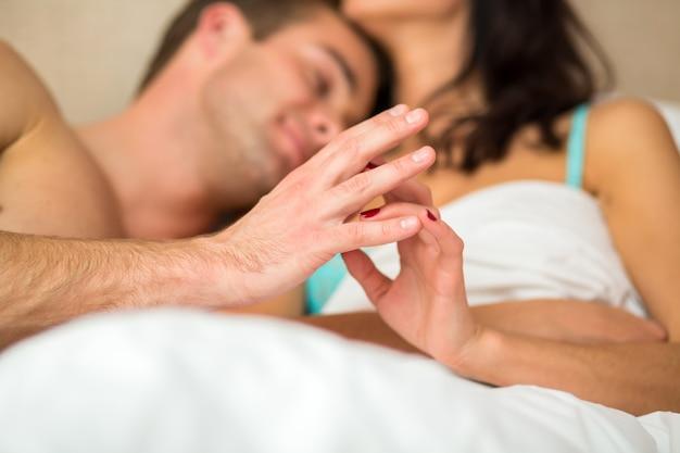 Пара трогательно руки в постели.