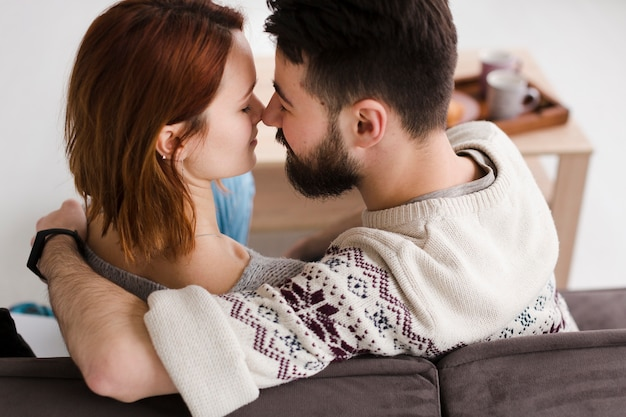 Couple touching noses from behind view
