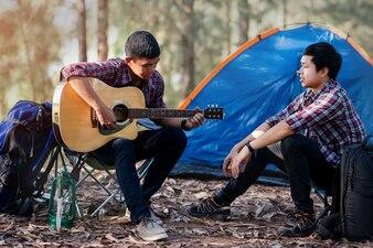 キャンプのアコースティックギターの時間を再生するカップルの観光客