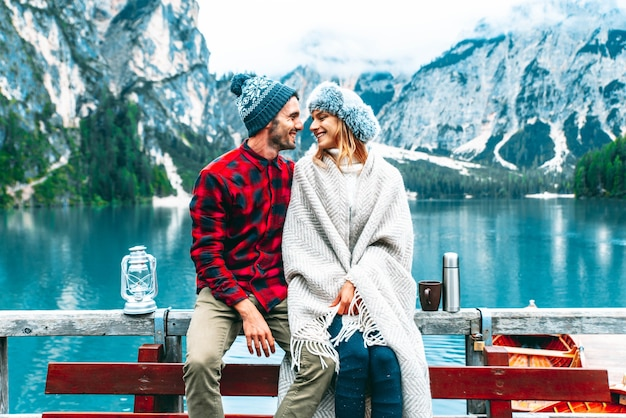 Couple of tourist visiting an alpine lake in braies, italy
