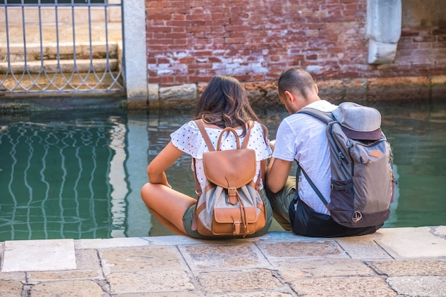 Couple of tourists are sitting by the canal in venice, italy.