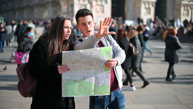 Couple of tourists in the city looking at a map and discussing about the next destination