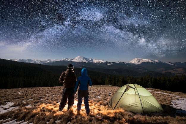 夜のキャンプでカップルの観光客