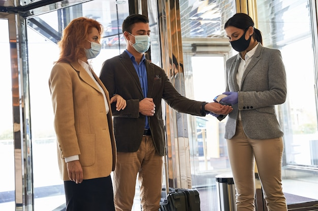 Couple of tourists in medical masks entering the hotel hall and a woman checking their temperature