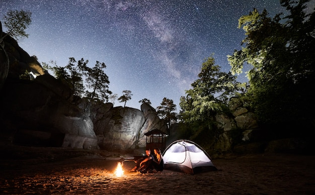 Couple tourists resting beside camp, campfire tent at night