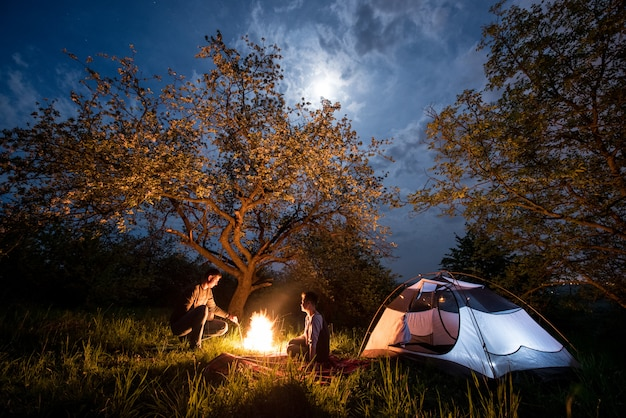 Couple tourists sitting at a campfire near tent under trees and night sky with the moon. night camping