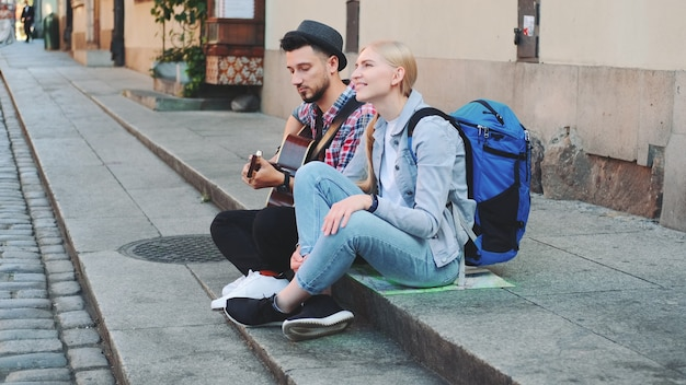 Couple of tourists sitting on sidewalk, playing guitar and having rest. sightseeing in beautiful european city.