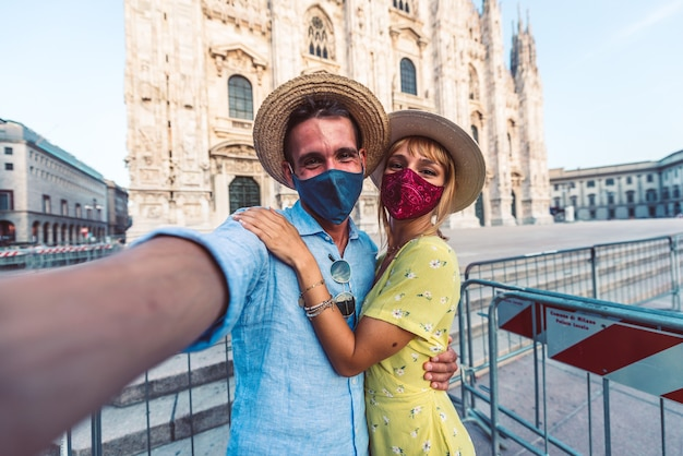 Couple of tourists wearing face mask tanking a selfie in front of the duomo of milan, italy