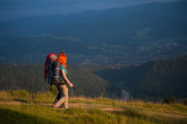 Couple tourists with backpacks holding hands, hiking, enjoying the view of beautiful open overlook on the mountains and village in the valley