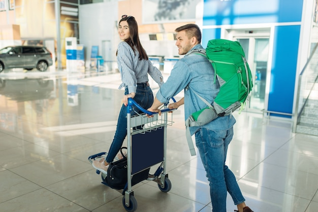Couple of tourists with cart and luggage in airport.