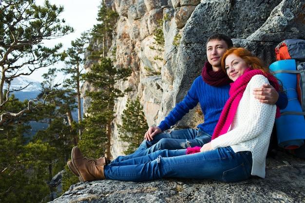 森と山のキャンプに座っているカップルの観光客の女性と男性