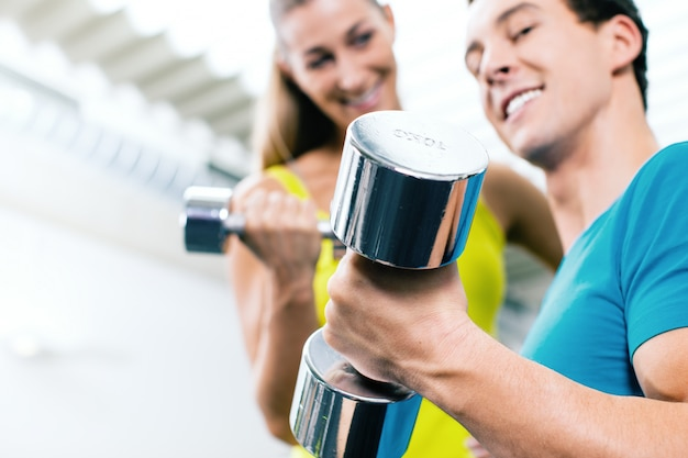Couple training for fitness in gym with weigts