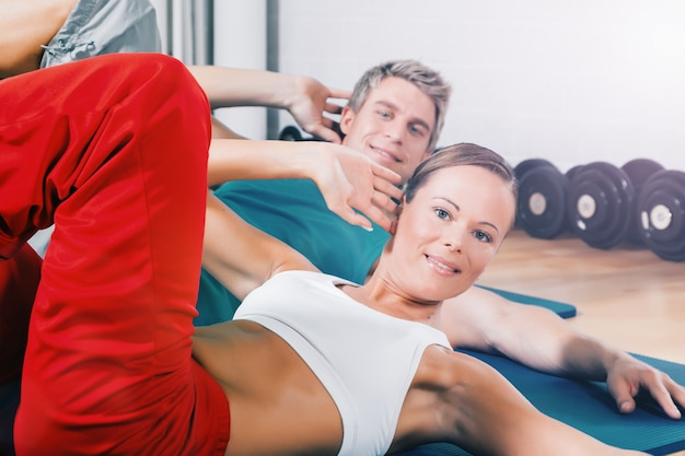 Couple training sit-ups in sport  gym