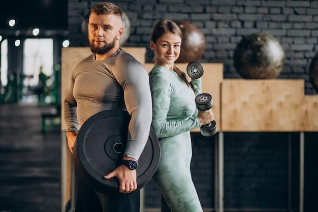 Пара тренируется вместе в тренажерном зале
