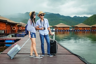 Couple traveler carry baggage on the wood bridge during vacation.
