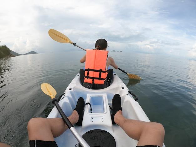 後ろから海で一緒にカヤックをするカップル旅行者。