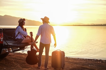 Couple traveler playing guitar and watching sunset near the lake