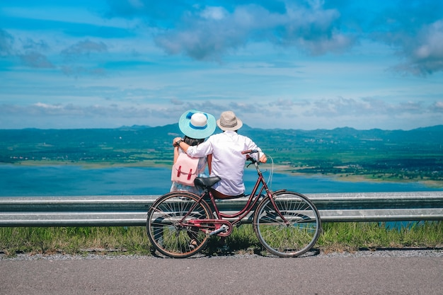 Couple traveler sitting beside bicycle background is mountain and dam