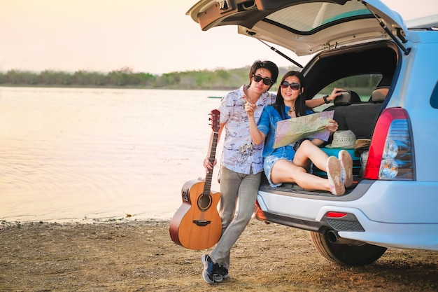 Couple of traveler sitting on hatchback of car and playing guitar near the road during holiday.