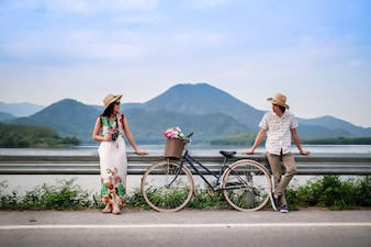 Couple traveler standing beside bicycle near the lake background is mountain on vacation.