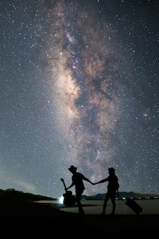 Couple traveler standing near the lake and looking milky way and stars on the sky
