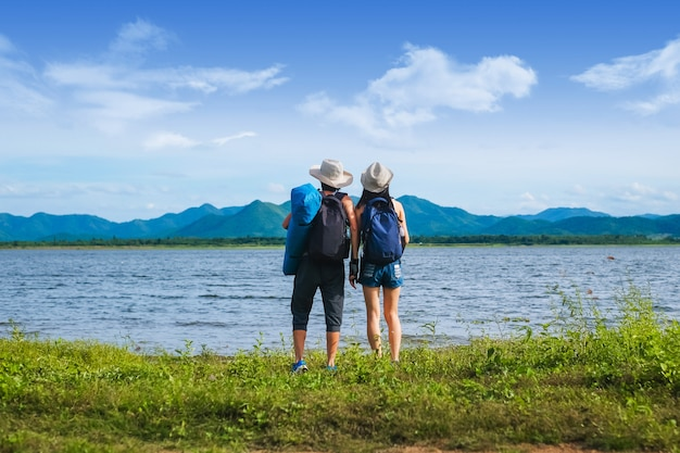 Couple traveler standing near the lake  in the mountain