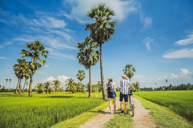 Couple traveler taking bicycle and looking for view of rice field..