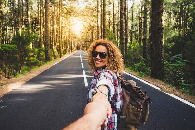 カップル旅行者の男性と女性は、長い道のりの森の風景と太陽で手をつないでフォローします。愛と旅行の幸せな感情ライフスタイルのコンセプト。アクティブな冒険休暇を旅行する人々
