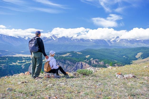 カップル旅行者男と女の山をリラックスした崖の上に座っています。山の上でリラックスし、谷の景色を楽しんでいるバックパックでハイカー。