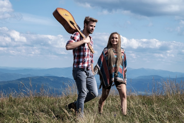 Couple travelers man and woman follow holding hands at sunny mountains landscape