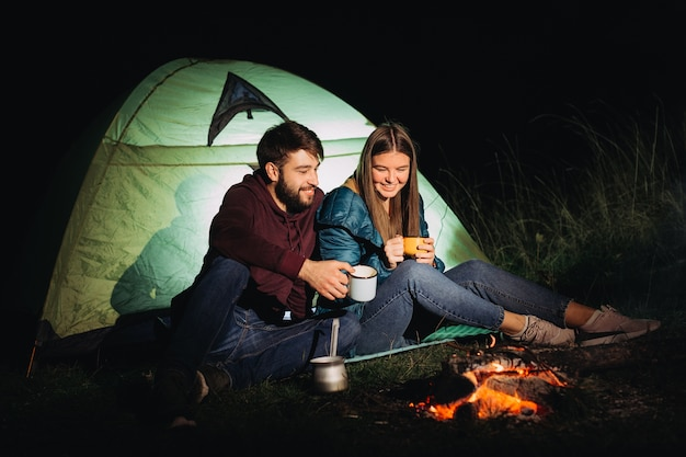 Couple of travelers sitting near bonfire