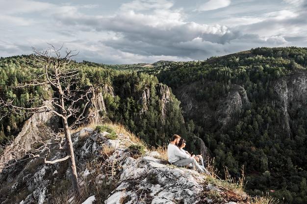山を旅するカップル。山の愛のカップル。男と女の旅行。山の散歩。愛好家は自然の中でリラックスします。山でのハイキング。