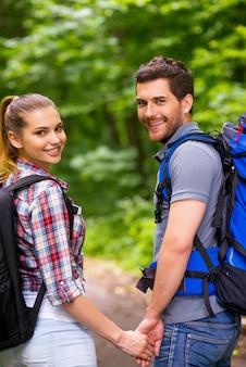 Пара путешествует с рюкзаками. счастливая молодая влюбленная пара несет рюкзаки и с улыбкой смотрит через плечо во время прогулки по лесной тропе