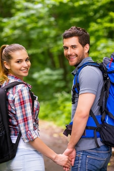 Couple traveling with backpacks. happy young loving couple carrying backpacks and looking over shoulder with smile while walking along the forest pathway