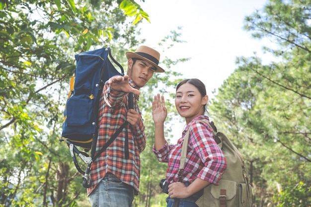 Couple on a trekking day in tropical forest along with backpacks in the forest, adventure, travel, tourism, hike.