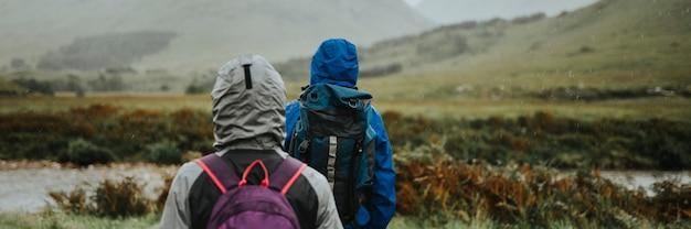 高地の雨の中をトレッキングするカップル